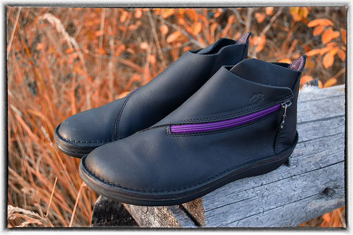 Women's black leather ankle boots with purple zipper in the rays of the setting sun